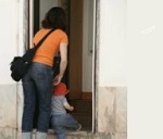 mother and child entering door community poverty
