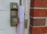 paper newsletter attached to screen door knob with rubber band