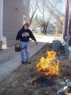 man supervising prescribed burn of native landscape beside his home