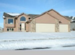 isolated large house with snow-covered yard and protruding garage