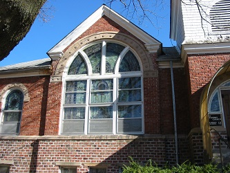 red brick church with beautiful large stained glass window and a bit of white frame belfry