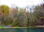 clean shimmering lake with autumn trees in background