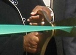 African American hands cutting green ribbon