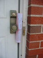 homeowner newsletter tied onto doorknob with rubber band