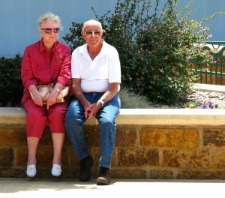 older couple resting on seating wall