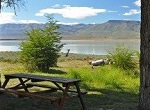 very clean empty picnic area by pristine lake with mountains in distance
