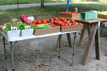peppers, tomatoes and squash at folder table at farmers market