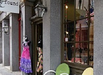 colorful shop with merchandise and chairs on sidewalk