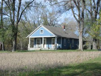pastel blue frame home in rural setting