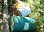 three drums casually disposed of, one of which is rusty