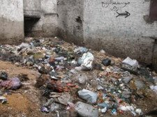 trash strewn alley points out need for derelict property clean up project