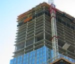 tall building being constructed and oriented to transit stop