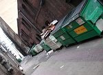 large dumpsters situated in wide alley