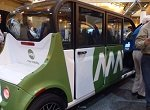 green and white self-driving car on convention floor