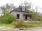 house with missing windows and disorderly vegetation