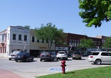 row of storefronts in smaller city with parking area in front
