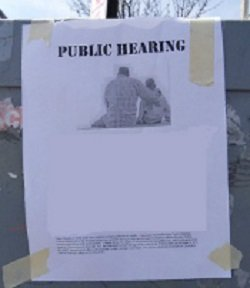 black-and-white flyer for a public hearing taped to utility box