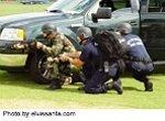 armed swat team crouching behind vehicle