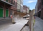 dumpster with construction debris in narrow street New Orleans
