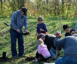 children and an adult planting tree