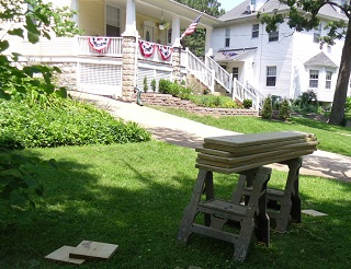 sawhorses and lumber on lawn as housing renovation proceeds