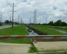 rusty bridge railing and under-maintained levee are infrastructure issues