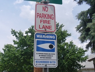 neighborhood watch sign posted in residential area under street sign