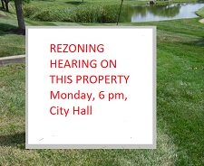rezoning hearing notice sign on lakeside commercial property
