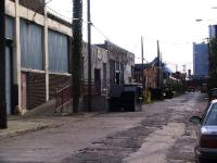 poorly maintained alley behind old commercial and industrial buildings