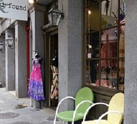 retail stores with colorful sidewalk display and outdoor chairs New Orleans