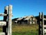 farm buildings seen through open gate in rural neighborhood