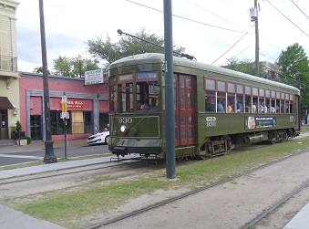 Saint Charles streetcar in New Orleans near stop with commercial activity
